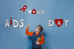boy with glasses holding a book pointing up International AIDS D - stock photo
