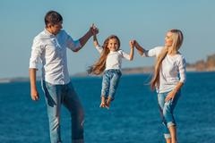 Happy family who playing on the beach. Concept of friendly familys Stock Photos