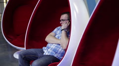 Man talking on the phone in an egg-shaped chair Stock Footage