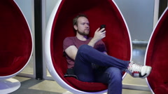 Man writes sms in an egg-shaped chair Stock Footage