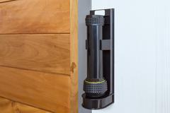 Emergency flashlight at door for urgent case Stock Photos