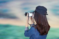 woman traveler wearing blue dress as photographer, take photo with camera out - stock photo