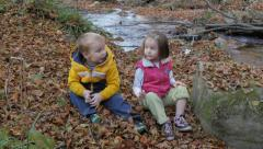 Two little children sitting, talking and playing with fallen leaves by the creek Stock Footage