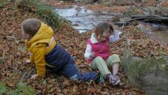 Two little kids play by the river and then stand up and go away, autumn season. - stock footage