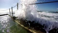 Wave breaks into ocean pool in slow motion Stock Footage