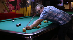 Billiards player pockets any ball in the hole - stock footage