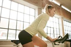 Stock Photo of Woman working out on a stationary bike