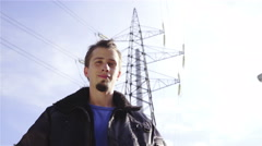 Man portrait shot in front of electric tower 4K Stock Footage