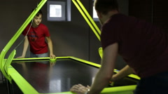Teen with man playing air hockey game Stock Footage