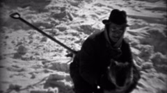 1936: Fedora hat man caring for dog in winter snowscape scene.  SAXTON, Stock Footage