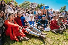 Participants of festival of medieval culture resting on grass in - stock photo