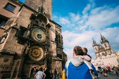 The unrecognizable man and boy are looking at astronomical clock Stock Photos