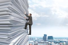 Businessman climbing up a huge stack of paper Stock Photos