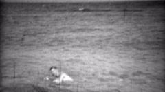 1936: Man swimming in underwear pulling it up along ocean beach.  BILOXI, Stock Footage