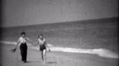 1936: Sisters walking together on beach in swimwear fashion and high pants. Stock Footage
