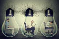 Company employees sitting in row inside electric lamp light bulb using laptop Stock Photos