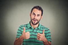 Happy man giving thumbs up sign. Positive human face expression body language Stock Photos