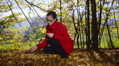 Woman in red playing with leafs in forest 4K  Stock Footage