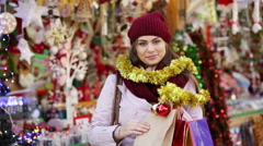 Beautiful woman choosing Christmas decoration - stock footage