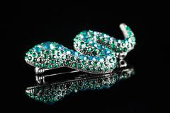 brooch in the form of a snake. green stones. black background - stock photo