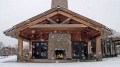 Ski Lodge with Outdoor Fireplace During a Snow Storm Stock Footage