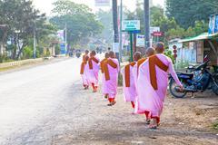 Stock Photo of MANDALAY, MYANMAR- NOVEMBER 24 :The buddhist nuns are walking along a street