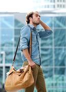 Male fashion model posing with leather bag - stock photo
