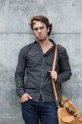 Male model posing with leather travel bag - stock photo