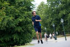 Young man running on footpath - stock photo