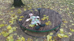 Rag doll placed on old children playground equipment in autumn Stock Footage