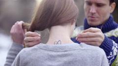 Man puts pendant around girls neck 4K - stock footage