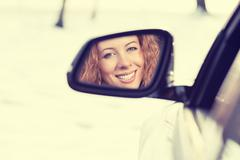 Happy young woman driver reflection in car side view mirror. Positive human f - stock photo