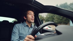Happy man whistling while driving car - stock footage