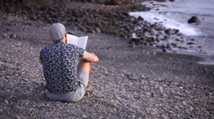 A guy with flat cap reading a book sitting on the beach Stock Footage