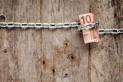 Stock Photo of Rolled up Ten euro bills in chains