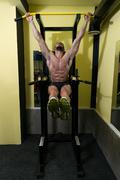 Young Man Performing Hanging Leg Raises Abs Exercise Stock Photos