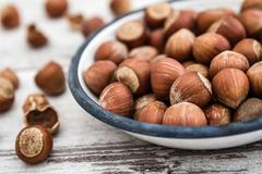 Hazelnuts in Enamel Bowl on White Wooden Table - stock photo