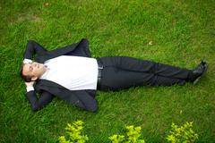Young businessman in a suit lying on the grass, view from above Stock Photos