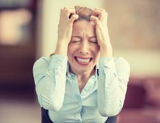 Portrait stressed crying screaming young woman in corporate office. Urban lif Stock Photos