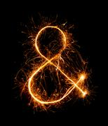 ampersand symbol  made of firework sparklers at night - stock photo