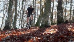 Mountain bike rider goes trough the autumn forest - stock footage