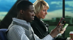 2 airline passengers using electronic devices at the airport Stock Footage