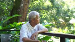 Asian senior guy thinking and worry in green lush nature background Stock Footage