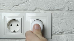Closeup of a man's hand inserting an electrical plug into a wall socket. - stock footage