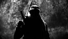The terrorist with an automatic rifle looks in the camera Stock Footage