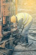 Worker add a length of pipe - stock photo