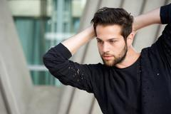 Handsome male fashion model posing with hands behind head - stock photo
