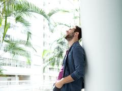 Happy young man leaning against wall in bright building - stock photo