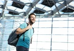 Happy man traveling with bag in airport Stock Photos