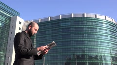 Business person in front of office checking latest information on newspaper 4K Stock Footage